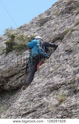 The rock-climber climbs a rock slope in Sudak, the Crimea
