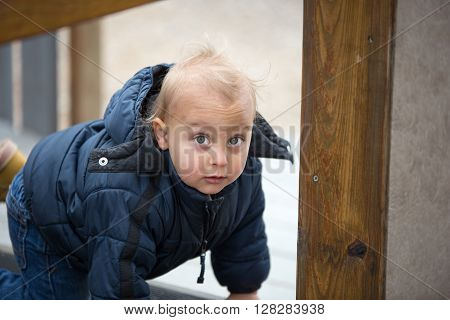 Toddler boy playing on playground equipment looking at camera.
