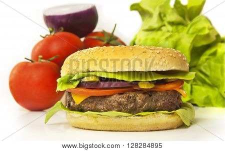 A photo of a burger with leaves of green lettuce slices of Cheddar cheese gherkins red onions tomatoes and a thick meat patty with blurred vegetables in the background