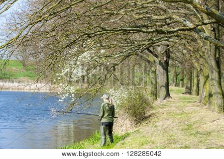 woman fishing at pond in spring