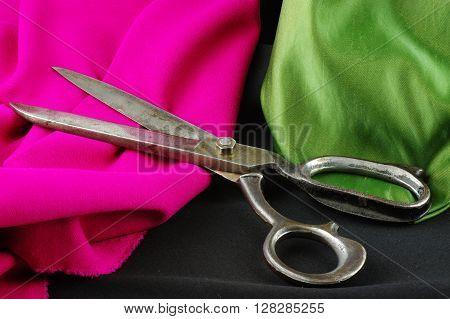 Old dressmaker scissors on a colored, creased fabrics.