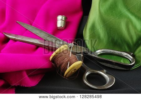 Old garment scissors, wooden spool of thread with a needle and a thimble. On a colored, creased fabrics.