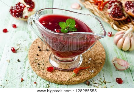Fresh pomegranate sauce for meat on a wooden table. Sauce made from red wine and pomegranate juice