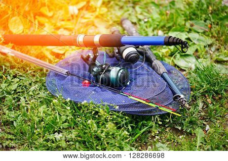 Fishing rods and tackle for fishing. Lays on a green grass