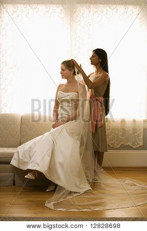 Indian bridesmaid placing veil on Caucasian bride.