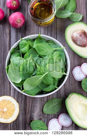 Fresh spring baby leaves of spinach with water drops in bowl, avocado and lemon, on a old grungy table