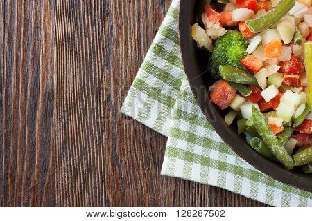 A mixture of assorted frozen vegetables in pan ready for cooking on brown wooden table