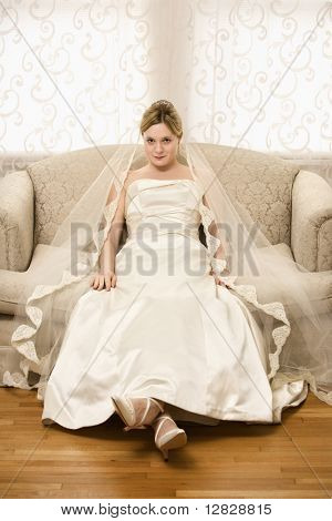 Caucasian bride slouching in love seat.