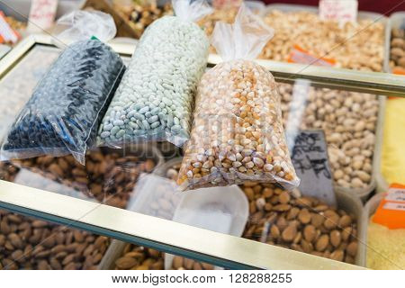 Packets of dried beans on a glass counter in a market in Paris, France
