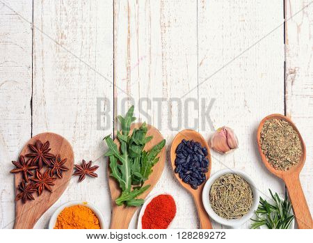 Fresh and dried herb and spice sampler on wooden background