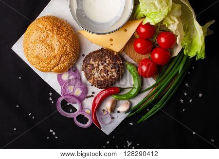 Exploded view of a hamburger on a black background. Ingredients. The process of assembling a hamburger. Top view. From above.