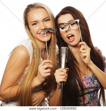 two young hipster blond girls singing, over white background