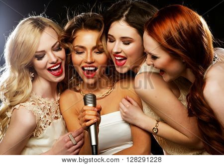 Four beautiful stylish girls singing karaoke at the club