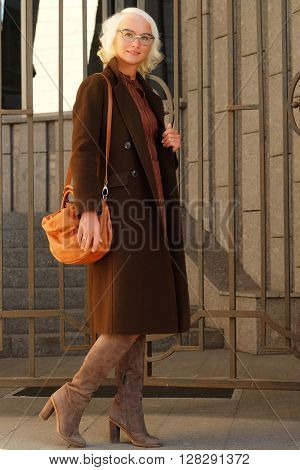 lifestyle fashion portrait of young stylish  woman walking on the street, wearing cute trendy outfit