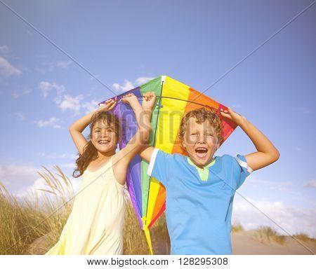 Cheerful Children Playing Kite Outdoors