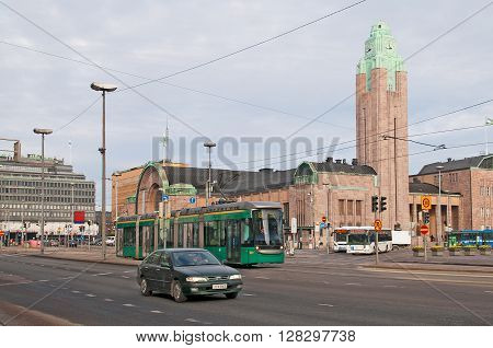 HELSINKI, FINLAND - APRIL 16, 2011: City transport near The Central Railway Station. The Railway Station Building was designed by Eliel Saarinen in Art Nouveau Style and opened in 1919.