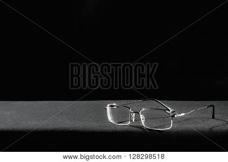 Eye glasses lying on the black table.