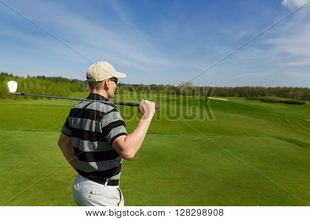 male golfer relaxes at fairway during a sunny day, back view