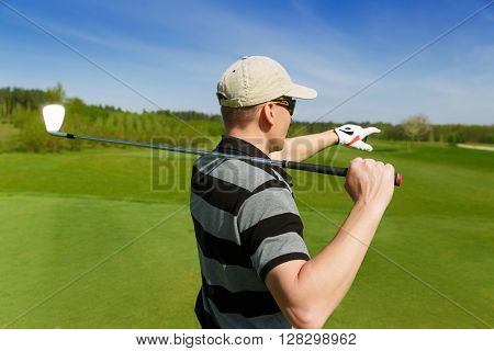 male golfer pointing at putting green, back view