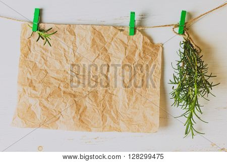 Banch of rosemary and paper hanging on white background . Toning