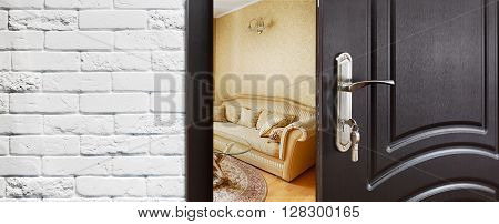 Half opened door to a living room. Door handle, door lock. Lounge door half open. Opening door. Privacy, safety concept. Entrance to the room. Door at white brick wall, modern interior design.