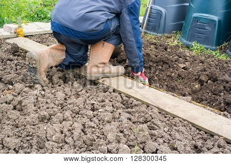 Gardener weeding an allotment in the Spring