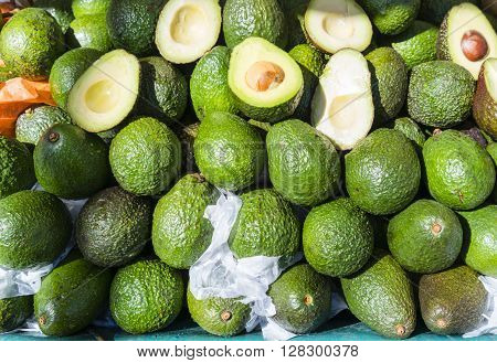 Avocados, whole and halved in French market. Suitable as pattern or background.
