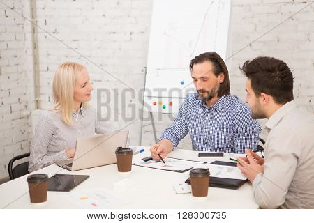 Businessteam of big company having meeting in board room and discussing business projects and strategies in office.