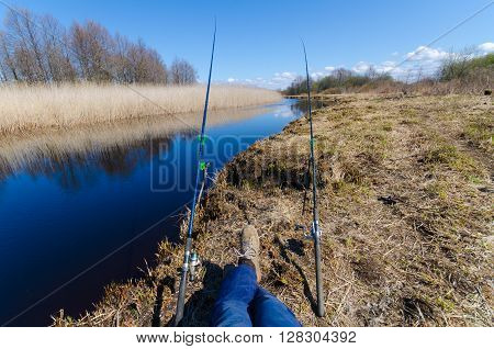 Eye view of fisshing process. Fisherman sitting on the river with two fishing rods. Sunny fishing day on the rever. Mans weekend.