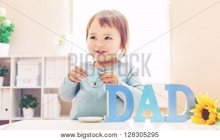 A happy toddler girl celebrating Father's Day