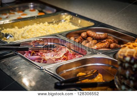 Hot counter containing warm breakfast items such as scrambled or fried eggs, bacon, sausages and others in a self service restaurant in a hotel