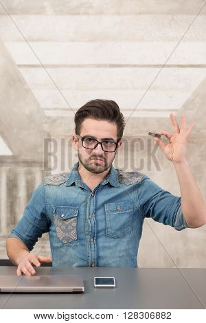 Freelancer holding usb card in office demonstrating digital storage. Handsome man in glasses looking at camera.