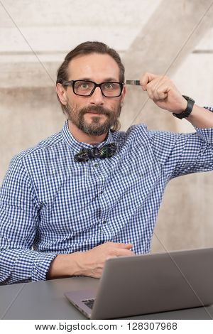 Handsome freelancer in glasses looking at camera and holding usb card near his head in office. Memery and storage concepts.