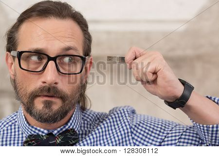 Close-up picture of handsome freelancer in glasses holding usb flash card and looking away. Storage, data, memory concepts.