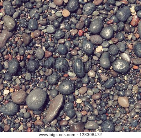 Toned colorful round sea stones on the beach of Santorini island can use as abstract background