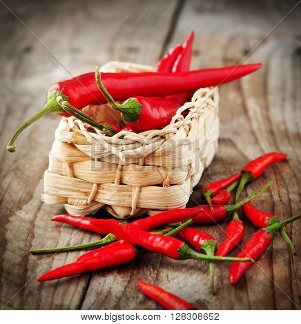 Fresh red chill peppers in small basket