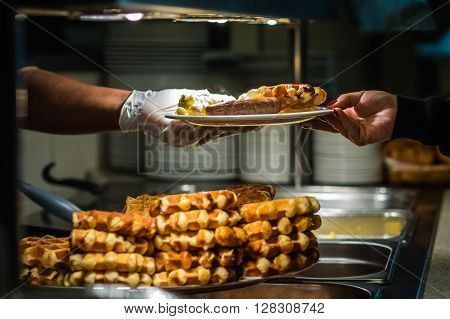 Hands of a person serving breakfast in a hotel restaurant