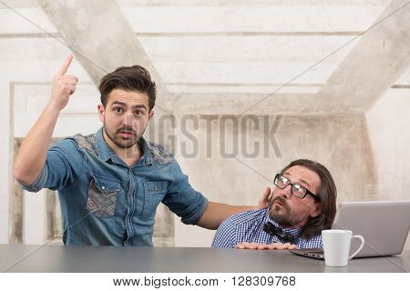 Frightened boss sitting under table and hiding from tax office while his worker explaining how to behave in difficult situations.