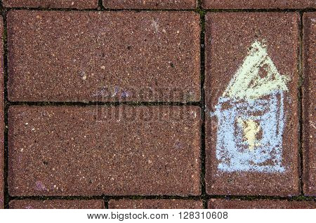 Childish chalk drawing of a house on a brick pavement