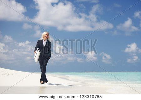 Business woman with briefcase walking on ocean beach