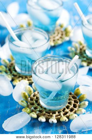 Glasses of Blue Curacao cocktail on wooden table