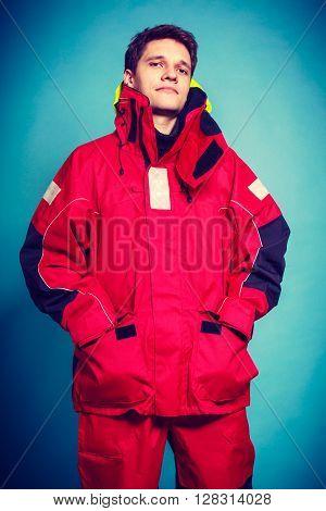 Firefighter in waterproof clothing. Studio shot on blue.