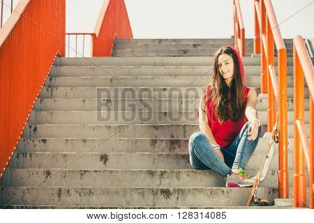 Cool skater young long haired girl with skateboard sitting on the urban stairs. Active lifestyle funky in summer. Outdoor trendy sport teenage. ** Note: Soft Focus at 100%, best at smaller sizes