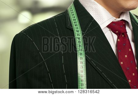 Tailor concept.  Businessman getting measured by a tailor