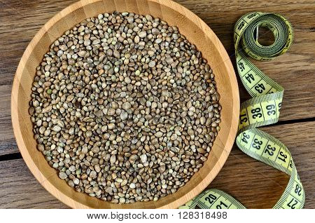 Hemp seeds in a bamboo bowl with centimeter on wooden table
