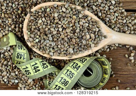 Healthy hemp seeds in a wooden spoon with centimeter on table