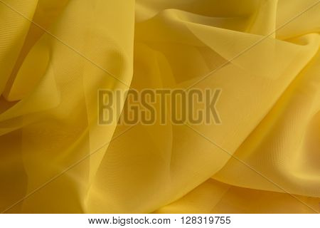 delicate yellow silky fabric folds background texture