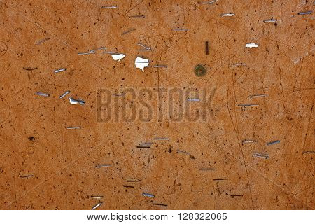 Old worn bulletin cork board with staples