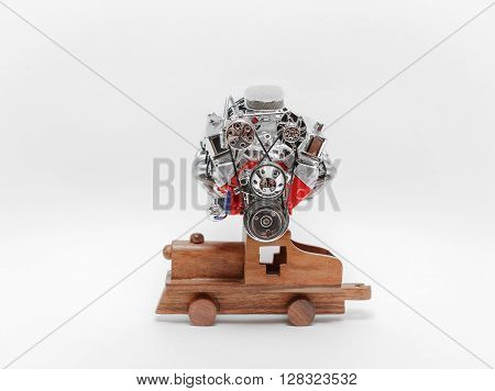 Old truck engine sitting on wooden vintage toy train against light-grey background