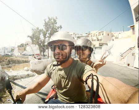 Young couple while taking a Selfie by quad in Santorini Island